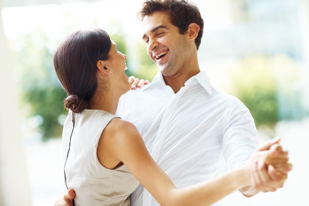Portraot of romantic young couple dancing and laughing - Outdoors